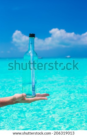 Bottle with a message in the hand background blue sky - stock photo
