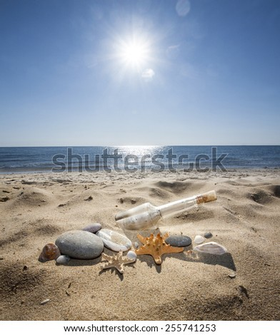 bottle with a message on the sea beach - stock photo