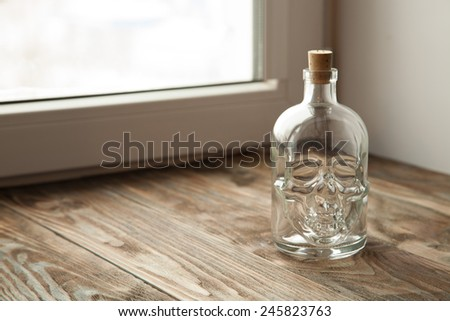Bottle with a skull on a wooden table - stock photo