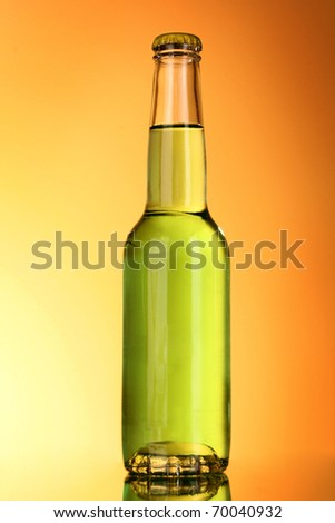 Bottle with alcohol on yellow background - stock photo