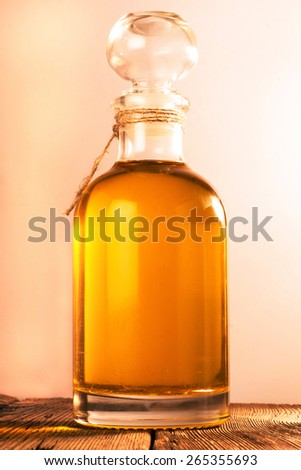 Bottle with  oil on a wooden surface - stock photo