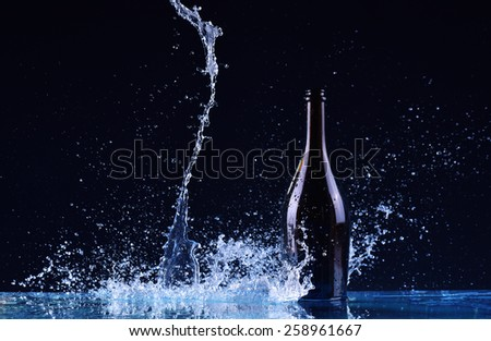 bottle with red white wine, water splash, wine on table on dark black background, big splash around bottle of red white wine splash on black - stock photo