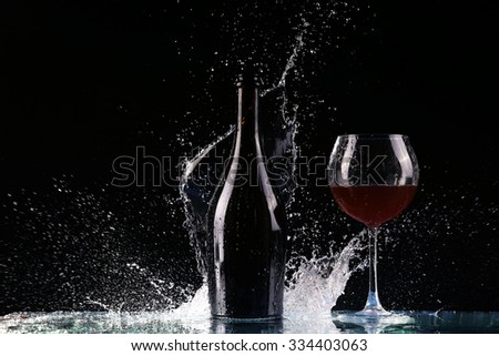 bottle with red wine, water splash, wine on table on black background, big splash around bottle of red wine  - stock photo