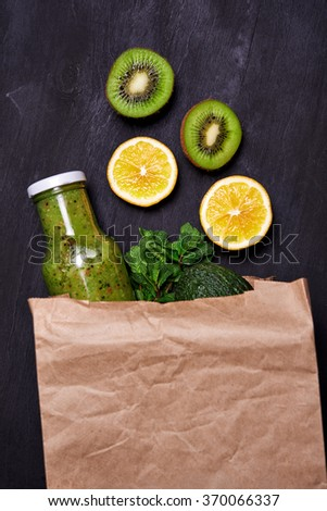 bottle with smoothie and fruits in paper bag. top view - stock photo