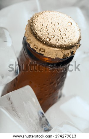 Bottle with soft drinks or alcohol in the ice. On gold caps and a bottle neck are drops of dew. Macro.  - stock photo
