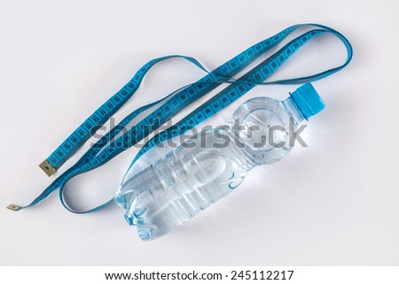 Bottle with water and measure tape on white background - stock photo