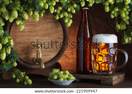 Bottled and unbottled beer with barrel and fresh hops for brewing still-life - stock photo