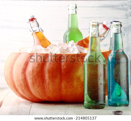 Bottled Beverages Chilling in Pumpkin Ice Bucket - stock photo
