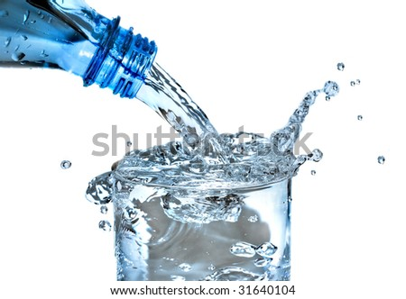 Bottled water being poured into a glass against white background - stock photo