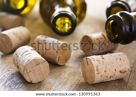 bottles and corks on wooden table - stock photo