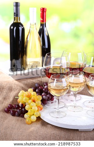 Bottles and glasses of wine and ripe grapes on table on natural background - stock photo
