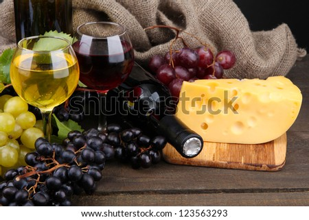 bottles and glasses of wine, cheese and grapes on grey background - stock photo