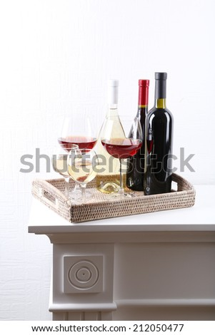 Bottles and glasses of wine on table in room - stock photo