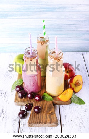 Bottles of delicious smoothie on table, close-up - stock photo