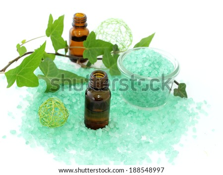 Bottles of essential oil, bath salt and branch of ivy isolated on white background  - stock photo