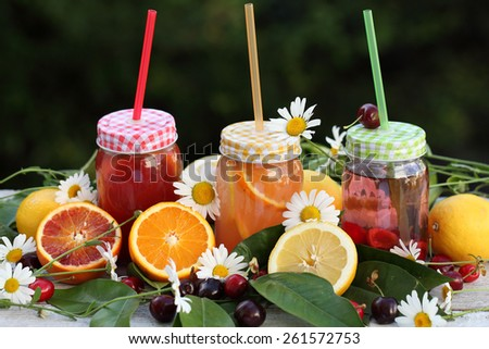 Bottles of freshly squeezed orange and berry juice standing on a tray with fresh fruits, green leaves and flowers daisies - stock photo