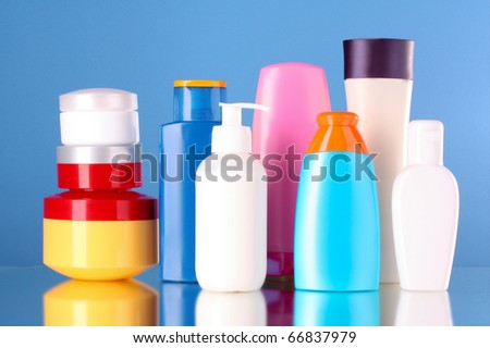 bottles of health and beauty products on blue background - stock photo