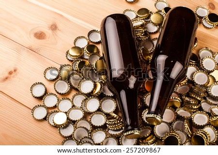 bottles  of homemade beer  and bottle caps on table - stock photo