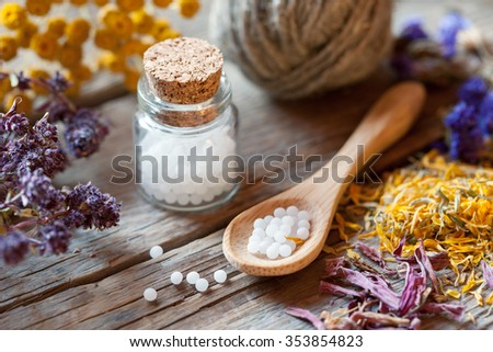 Bottles of homeopathy globules, spoon and healthy herbs. Selective focus. - stock photo