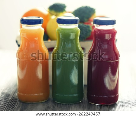 Bottles of juice with fruits and vegetables on table close up - stock photo