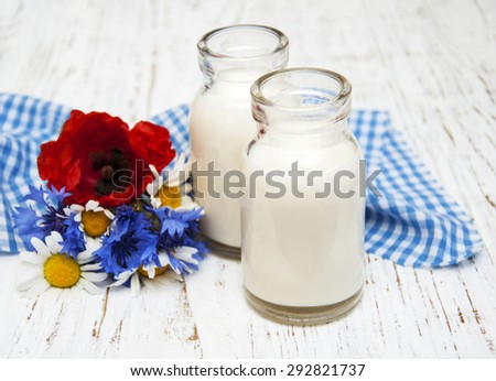 Bottles of milk and wildflowers on a old wooden background - stock photo
