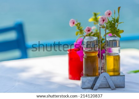 Bottles of Olive Oil And Vinegar On The Table With A Tablecloth Near The Sea in Greece - stock photo