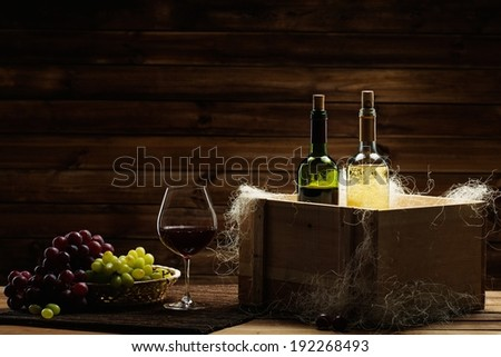 Bottles of red and white wine, glass and grape on a wooden interior  - stock photo