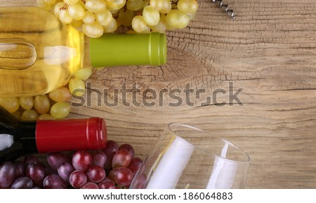 Bottles of red and white wine on old wood background. - stock photo