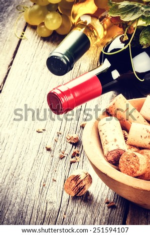 Bottles of red and white wine with bunch of corks  - stock photo