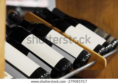 Bottles of red wine on a wooden shelf in the restaurant - stock photo