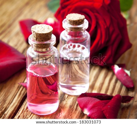 Bottles of Rose Essence with Petals, Flower Essential Oil In Transparent Little Bottles - stock photo