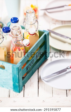 Bottles of tasty fresh homemade fruit juice and milk served in a colorful wooden crate on a picnic table with empty plates ready for a summer lunch - stock photo