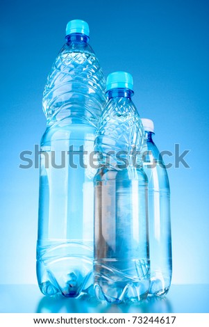 Bottles of water on blue background - stock photo