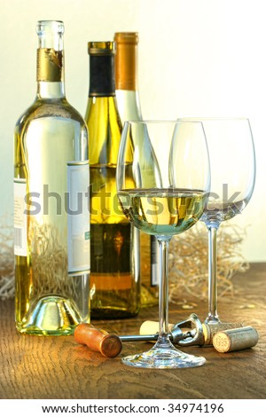 Bottles of white wine with glasses ready for wine tasting - stock photo