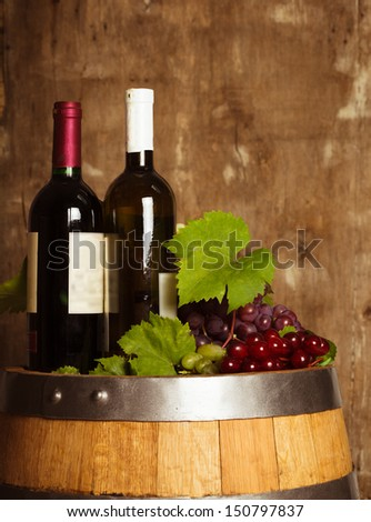 Bottles of wine on the oak barrel over old shabby wooden background - stock photo