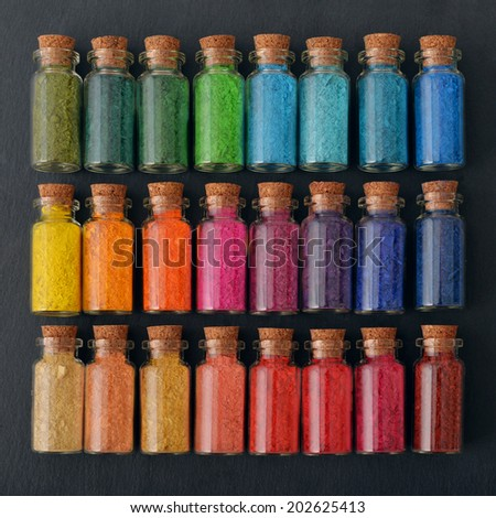 Bottles with colored powder dyes on a black background - stock photo