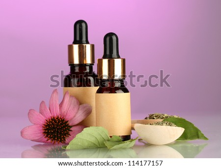 bottles with essence oil and purple echinacea, on pink background - stock photo