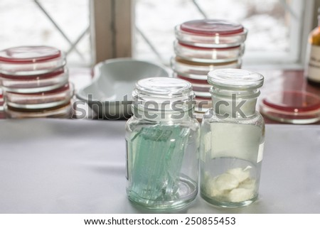 Bottles with glass pieces and swabs in a lab; Petri dishes stacked on the background. Medical tests and research. Hospital laboratory glassware. - stock photo