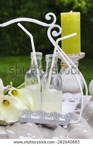 Bottles with lemonade and calla flowers in the garden - stock photo