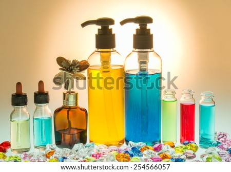 Bottles with natural aroma oil and body care product on backlight background - stock photo