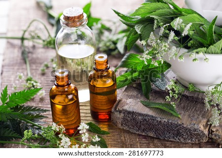 Bottles with organic essential aroma oil with mint  on aged wooden background. Selective focus.  - stock photo