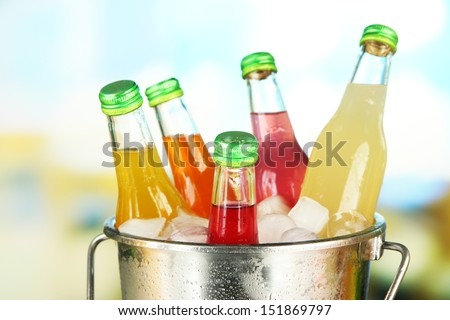 Bottles with tasty drinks in bucket with ice cubes, in bright background - stock photo