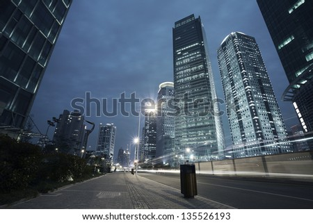 Bottom angle shooting highway car light trails of modern urban buildings - stock photo