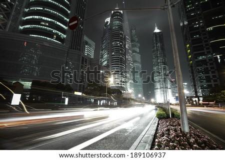 Bottom angle shooting highway car light trails of modern urban buildings   - stock photo