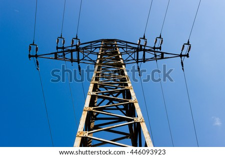 Bottom to top view high voltage tower (electricity post) against blue sky. - stock photo