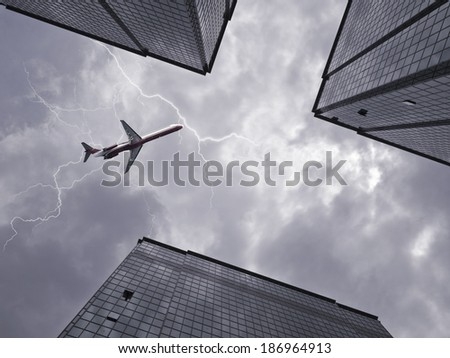 Bottom view of airplane flying above skyscraper in stormy sky - stock photo