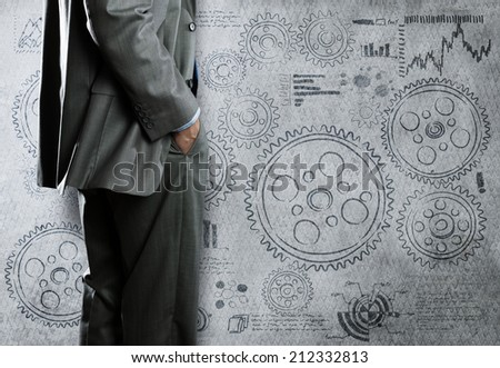 Bottom view of businessman and cogwheels on wall - stock photo