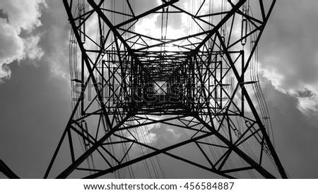 Bottom view of electric pole with beautiful sky in black and white shot. - stock photo