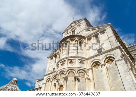 Bottom view of historical old Pisa Cathedral in Cathedral Square in Pisa, Italy, on cloudy blue sky background. - stock photo