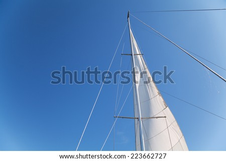 Bottom view of mast and sail of yacht on blue sky background - stock photo